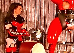Two mistresses in latex practicing cbt on their rubber male slave in dungeon