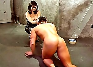 Hot domina feeding then spanking her restrained male slave in the dungeon