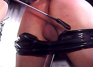 Topless mistress in sexy latex outfit puts her male slave on a saw horse and punishes his bare butt with a riding crop