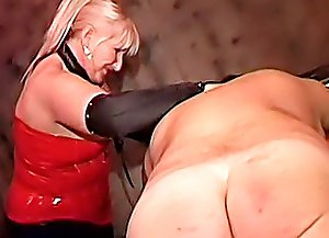 Submissive fat man stretched, spanked and lashed on a punishment table by a blonde mistress in sexy latex outfit
