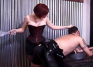 Two hot and unmerciful dommes make their male slave bend over and paddle his big latex clad ass with no merc