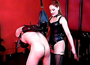 Restrained male slave in full leather hood bends over to take some bare butt spanking from his beautiful mistress
