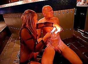 Mistress pours hot wax all over her bald slave's chest, cock and balls and whips his genitals with no mercy