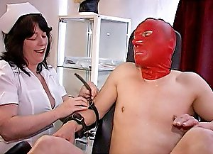 Kinky medical domme in white uniform using metal tools to punish masked slave's cock and balls in a painful way