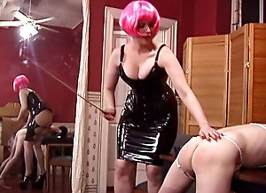Mistress in black latex dress and pink wig makes her male slave bend over a table and spanks his tender ass red
