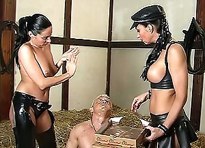 Two mistress in black leather make slave guy sit down onto the hay in dirty barn and shove food into his mouth